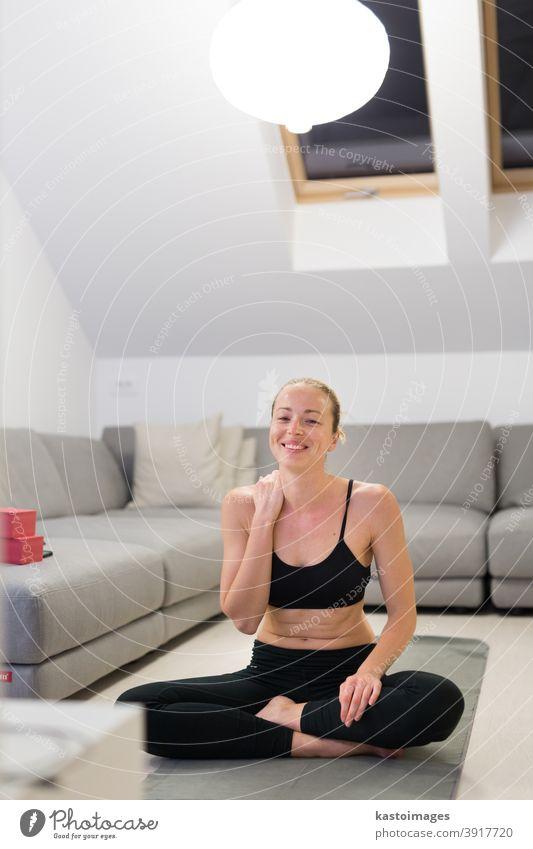 Schöne blonde Frau beim Heimtraining in der Halle. Frau praktiziert Yoga zu Hause. Fitness-Lehrgänge für einen gesunden, aktiven Lebensstil für Mädchen. Frau nutzt Quarantäne für Heimtraining.
