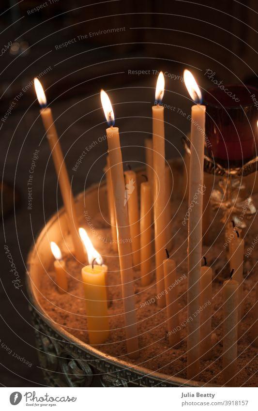 Anzünden von Bienenwachskerzen im Sand; orthodoxe Kirche Kerzen beleuchtet Licht Spitzkerzen zerlaufen Docht Flamme katholisch Gebet beten Kerzenschein Hoffnung