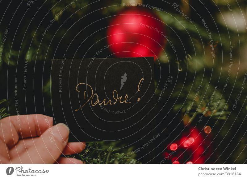 Hand hält ein schwarzes Papier mit der handgeschriebenen Aufschrift 'Danke' . Im Hintergrund rote Kugeln am Weihnachtsbaum danken Weihnachten Christbaumkugel