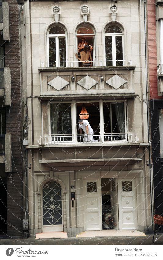 Eine zufällige Straßenfotografie-Aufnahme eines zufälligen Ereignisses im selben Haus. Im dritten Stock befindet sich eine oben ohne Frau, unten sieht man einige Handwerker bei ihrer Arbeit. Diese Aktion befindet sich irgendwo in den Straßen von Antwerpen, Belgien.