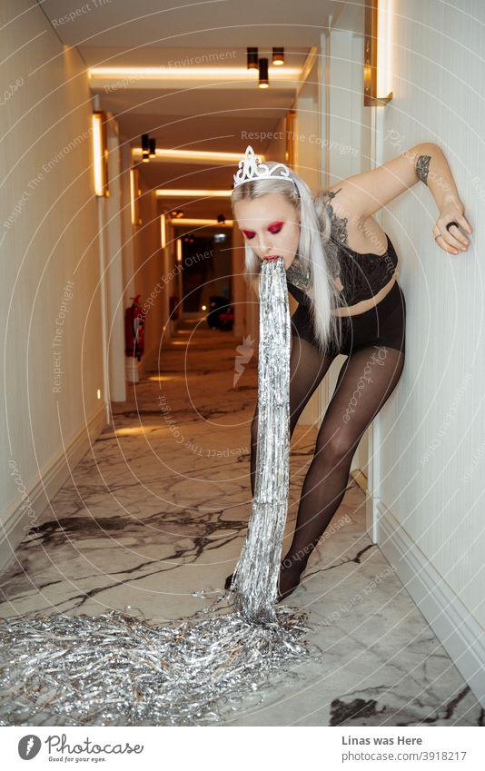 Ein wunderschönes getuschtes Mädchen in einem Korridor des Hotels, das Konfetti erbricht. Manchmal kann zu viel Freude an den Feiertagen krank machen. Girlanden