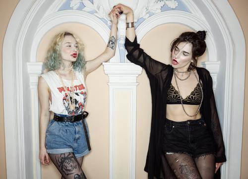 Junges Blut und positive Energie. Zwei wilde Mädchen mit Tattoos halten sich in einer schicken Villa mit stilvollem Interieur an den Händen. Mädchen wollen einfach nur Spaß haben!
