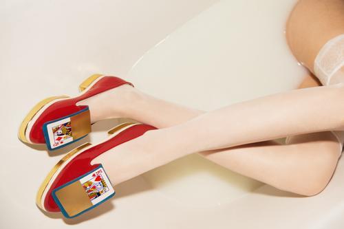 Diese Schuhe sind definitiv nicht für Spaziergänge auf dem Feld gemacht. Warum nicht stattdessen ein Milchbad versuchen. Ein Foto von stilvollen, goldenen, roten, avantgardistischen Frauenschuhen in einem Milchbad. Oh, und Sie können auch lange und wunderschöne Beine darin sehen.