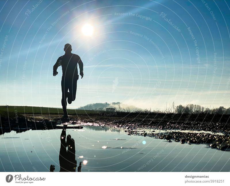 Winterlauf im Gegenlicht laufen Joggen trail Himmel Froschperspektive rennen sonnig sonniger Tag Außenaufnahme Natur Bewegung Waldrand Waldläufer Sport