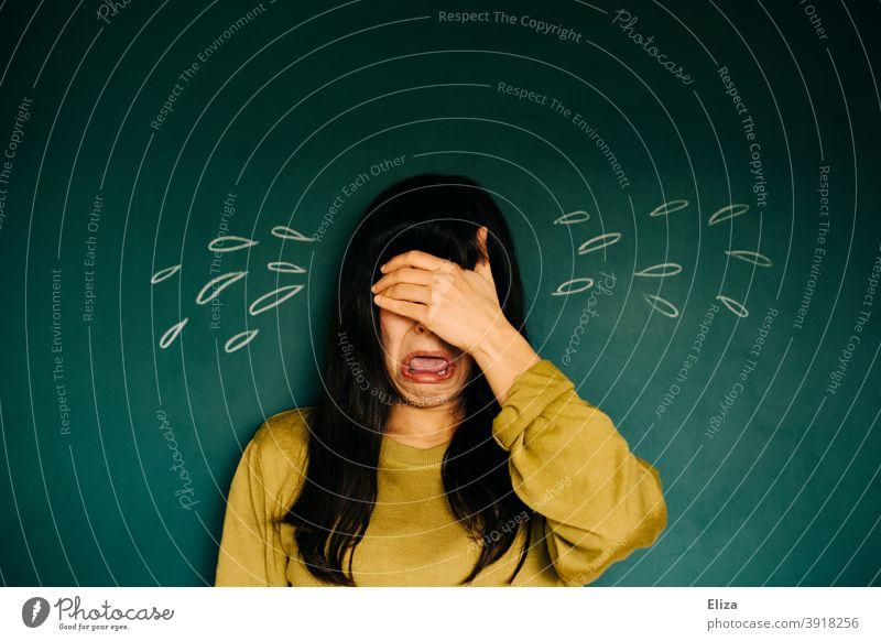 Junge Frau weint große (gemalte) Tränen und hält sich die Hand vor die Augen. weinen weinend dunkelhaarig überspitzt lustig Trauer Traurigkeit Verzweiflung