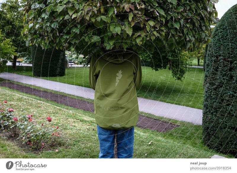 Kind versteckt sich in Baumkrone Natur Versteck verstecken Blätter skurril surreal Kopf grün Tarnung Spaß originell Außenaufnahme Freak Humor Ton in Ton