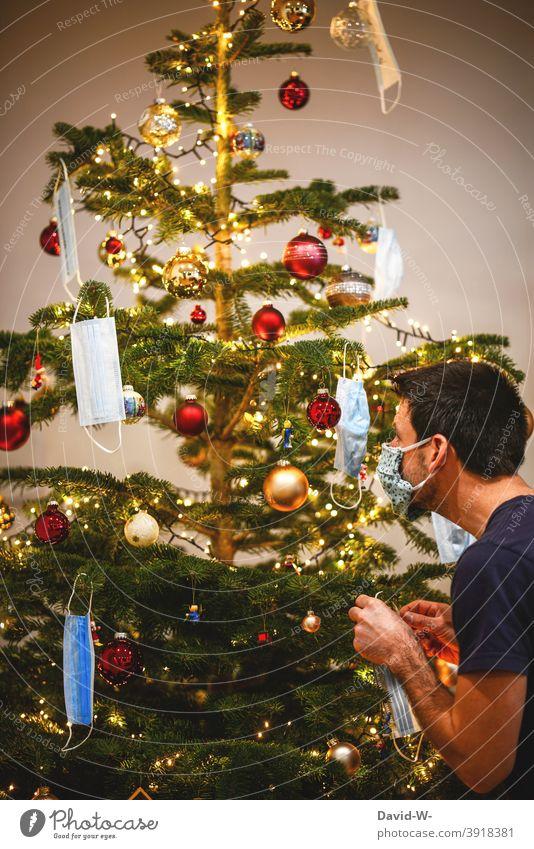 Corona - der Weihnachtsbaum wird geschmückt schmücken Christbaum Christbaumschmuck Maske Mundschutz Mann weihnachtsdekoration Pandemie schützen Coronavirus