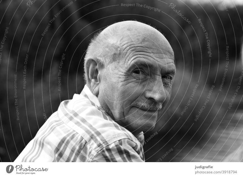Senior blickt freundlich über die Schulter in die Kamera Mann Portrait Männlicher Senior Mensch Großvater Erwachsene maskulin Außenaufnahme Schwarzweißfoto