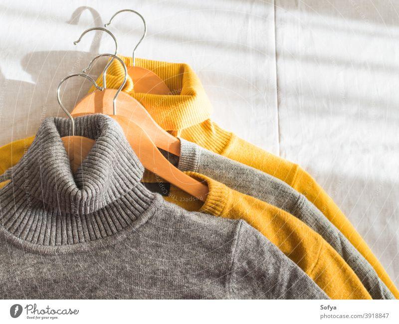 Gelbe Leuchtfarbe und graue Winterpullover Pullover gelb Herbst Kleiderbügel Kaschmiri fallen beleuchtet Hintergrund stricken gemütlich Mode warm Farbe