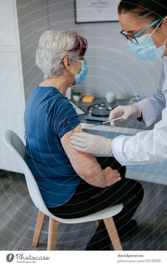 Seniorin wird gegen Coronavirus geimpft Impfung covid-19 geduldig älter Einspritzung Arzt Spritze medizinisch Gesundheitswesen Arme einspritzend Kur Menschen