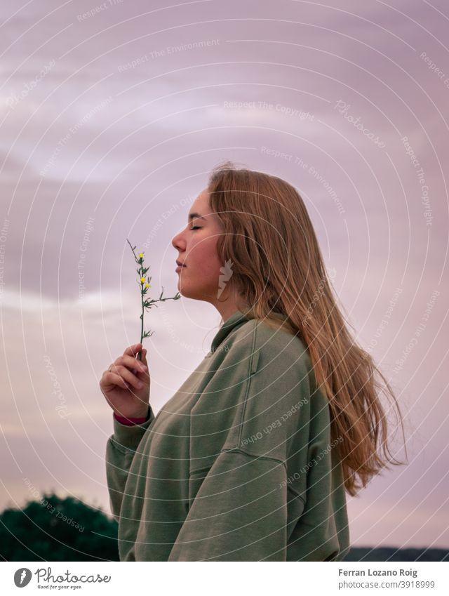 Porträt einer Frau, die an einer Blume riecht Behaarung braune Haare lange Haare geschlossene Augen riechen riechend rosa Himmel hoddie Blumen Natur Park