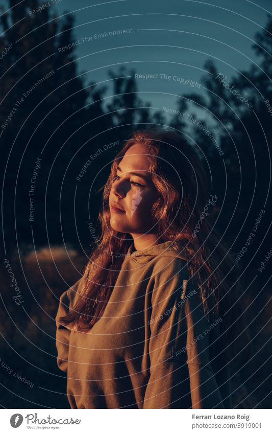 Porträt einer Frau im Sonnenuntergang orange Orangetöne Nachmittag Gesicht lange Haare Behaarung Frauengesicht Auge Kapuzenpulli