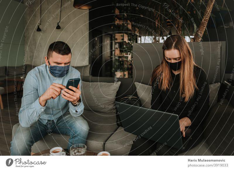 Menschen mit Gesichtsmaske, die in Innenräumen Laptop- und Smartphone-Technik nutzen Süchtige Erwachsener Anwendung attraktiv schön Business lässig Funktelefon