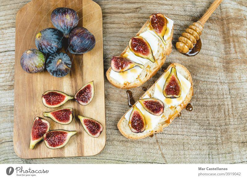 Feigen geschnitten auf Toast mit Käse. Zuprosten Brot Frühstück Snack reif Frucht ganz Küchentisch Holzboden Textfreiraum Draufsicht purpur geschmackvoll