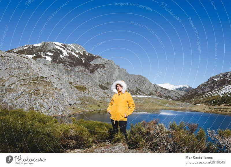 Berglandschaft mit verschneiten Bergen und See. Frau in gelber Jacke schaut in die Kamera. Aussehen gestellt kalt gelbe Jacke Wasser Landschaft Berge u. Gebirge