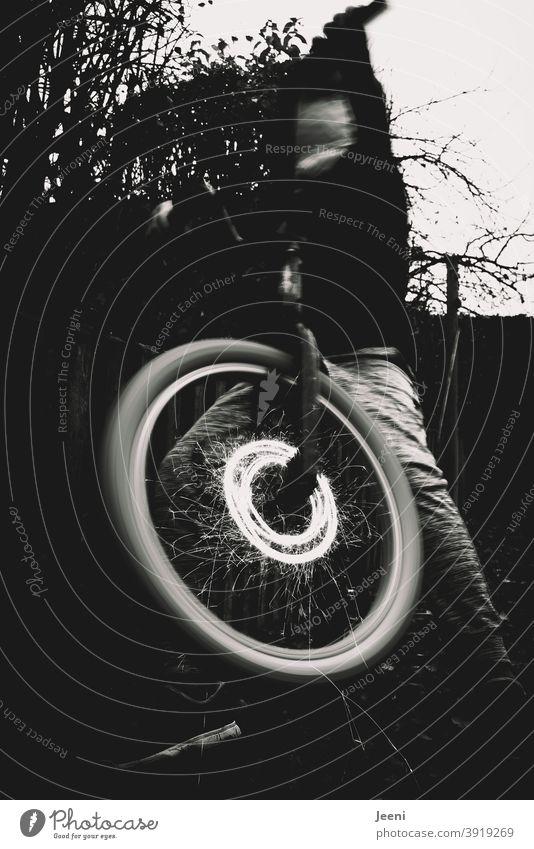 Hot Wheel | BMX-Rad dreht sich mit Funkenflug | Jugendlicher sitzt auf dem Fahrrad und hält den Lenker in die Höhe hot wheel heiß drehen Funkenregen funkeln