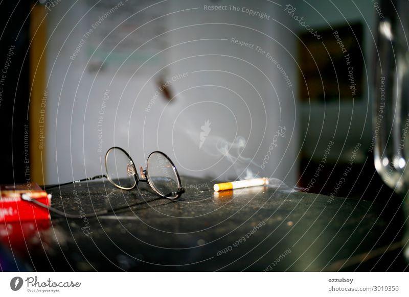 Zigarette und Brille auf dem Tisch Rauchen Sucht Tabak Tabakwaren Nikotin ungesund Unselbständigkeit gesundheitsschädlich Zigarettenrauch Nikotingeruch