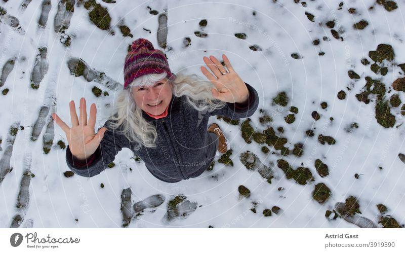 Drohnenaufnahme von einer Frau im Schnee die nach oben winkt frau winter schnee winken lachen luftaufnahme drohnenaufnahme drohnenansicht lustig spaß freuen
