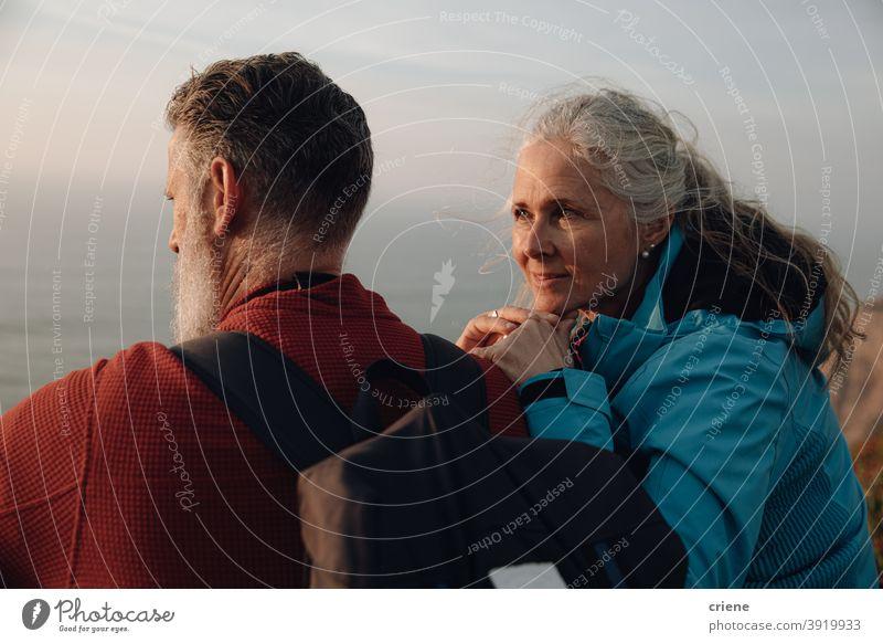 kaukasischen Senior Paar sitzt auf Klippe genießen Sonnenuntergang zusammen Liebe Frau Menschen Glück zwei alt Familie Romantik im Freien älter Zusammensein