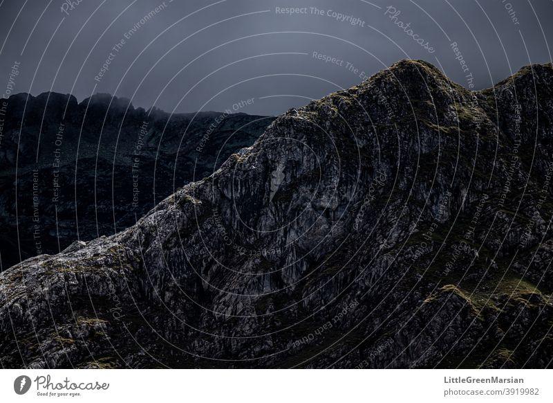 Beleuchtete Bergseite Berge u. Gebirge Licht Schatten Kontrast hoher Kontrast Dunkelheit Felsen Moos Gras Wolken Stein Bruchstein steil wandern alpin Landschaft