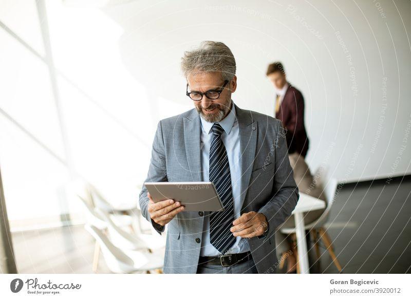 Gut aussehend reifen Geschäftsmann mit seinem Tablet im Büro Erwachsener Lebensalter allein attraktiv Business Geschäftsleute Karriere Kaukasier selbstbewusst