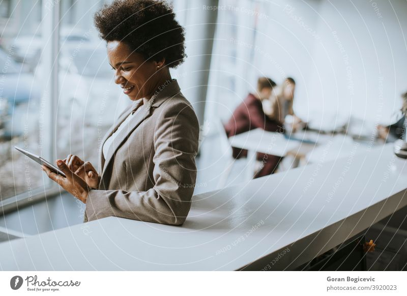 Afroamerikanische Geschäftsfrau stehend und mit digitalem Tablet in einem modernen Büro Erwachsener Afrikanisch Afro-Look Amerikaner schön schwarz Business
