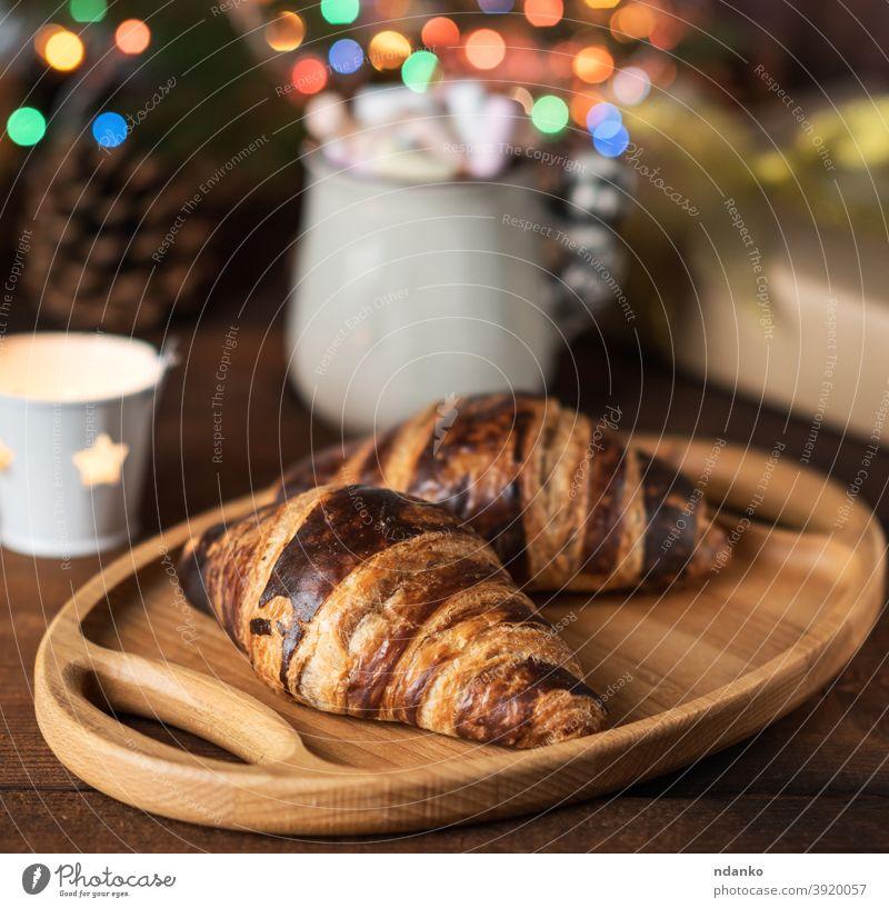 gebackene Croissants und eine weiße Keramiktasse mit Kaffee, hinter den brennenden Weihnachtslichtern Tasse Becher Neujahr Gebäck rollen rustikal Snack süß