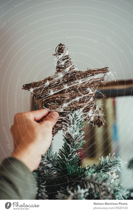 Nahaufnahme der Hand eines Mannes, der den Weihnachtsstern an den Baum hängt. Weihnachtsschmuck Weihnachtsdekoration erhängen verziert elegant vereinzelt