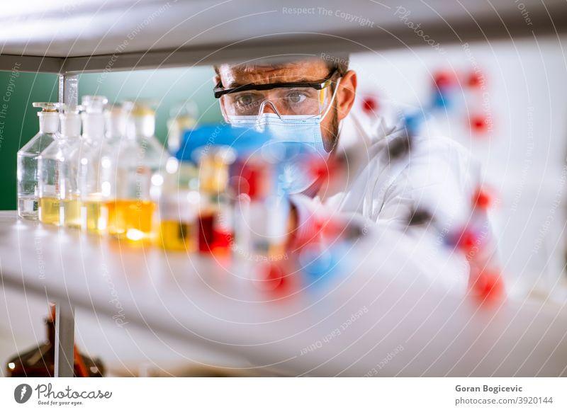 Junger Forscher mit Schutzbrille beim Prüfen von Reagenzgläsern Bildung Labor forschen Experiment Wissenschaft männlich Wissenschaftler wissenschaftlich Mann