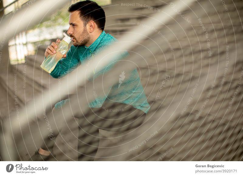 Junger Mann ruht sich während des Trainings mit einer Flasche Wasser aus Fitness männlich jung urban Sport passen Athlet aktiv sportlich Großstadt Gesundheit