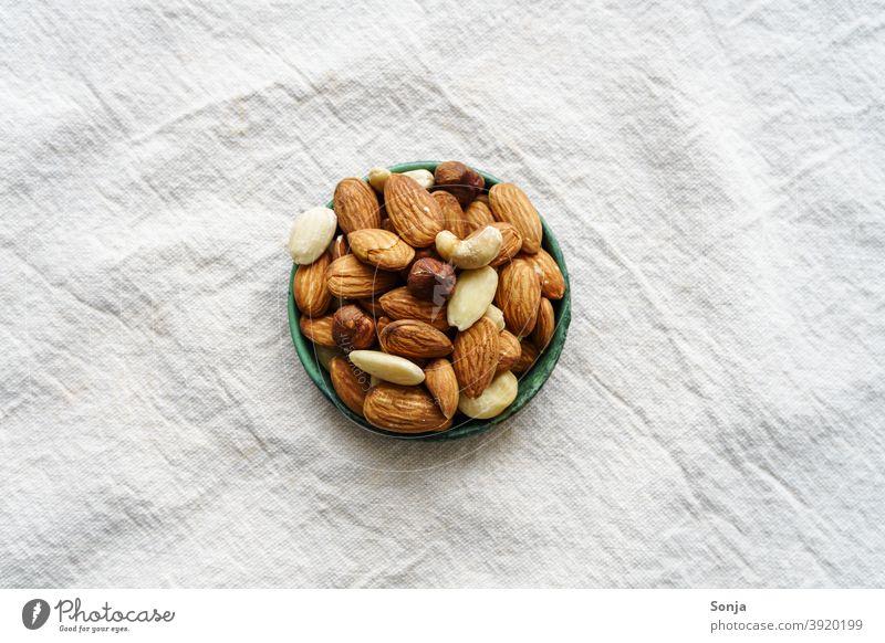Variation von Nüssen in einer Schüssel auf einem beigen Leinen Tischtuch. Draufsicht. variation tischtuch Protein Gesundheit lecker Lebensmittel frisch roh Diät