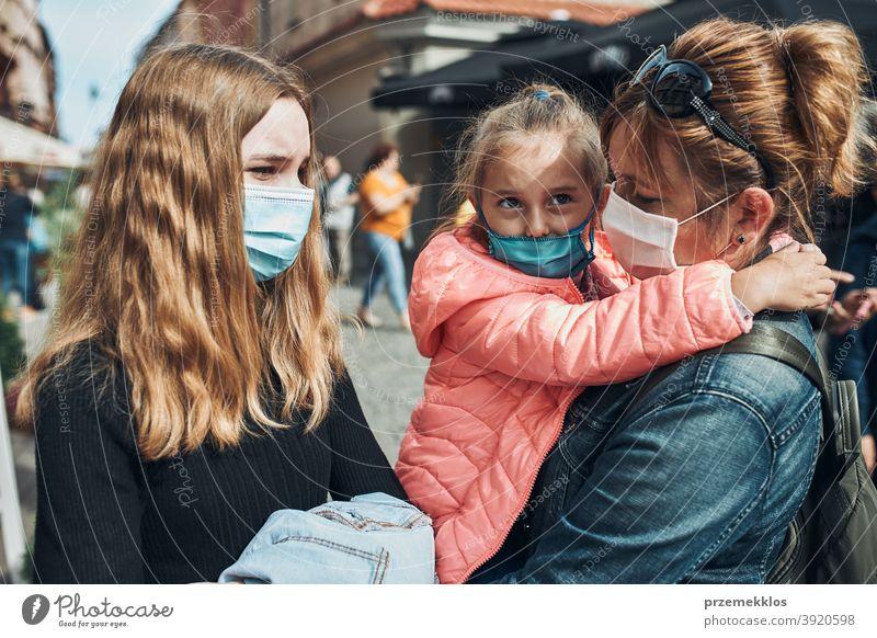 Familienmutter und ihre Töchter stehen in einer Straße in der Innenstadt und tragen die Gesichtsmasken, um eine Virusinfektion zu vermeiden Anruf Pflege