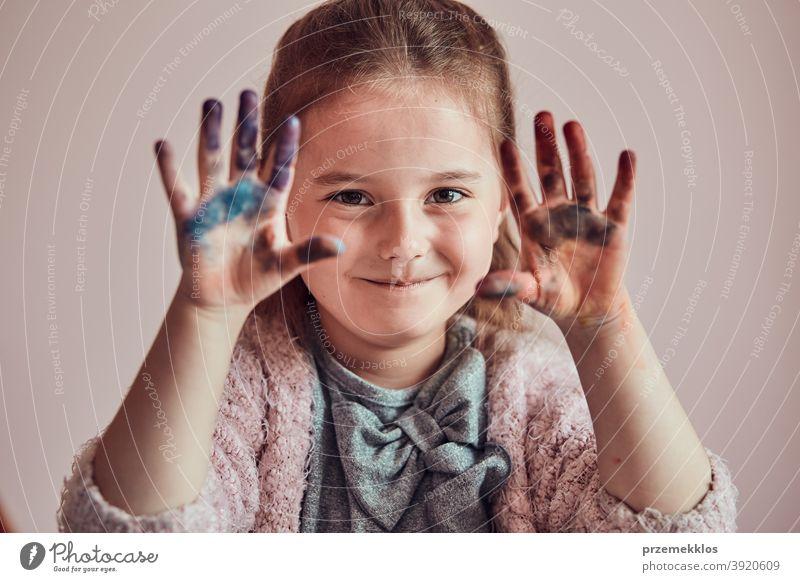 Kleines Mädchen im Vorschulalter mit bemalten bunten Händen Kind Malerei Farbstoff Bildung farbenfroh Kunst heimwärts Papier Kindheit Vorschule Schaffung