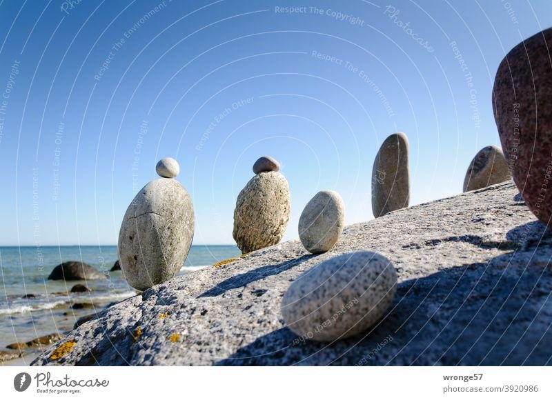 Steinmandl stehen auf einem großen Stein und blicken auf's Meer Steinmännl Steinmänner See Ostsee in Reihe stehen Strand Wasser Natur Küste