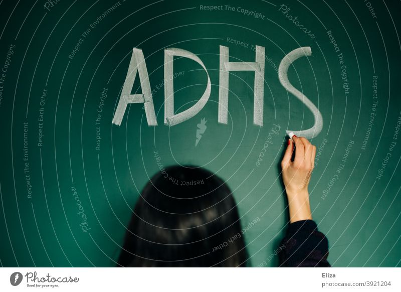 Eine junge Frau schreibt ADHS auf eine Tafel Störung Krankheit Aufmerksamkeitsdefizit Diagnose ADS Hyperaktivität