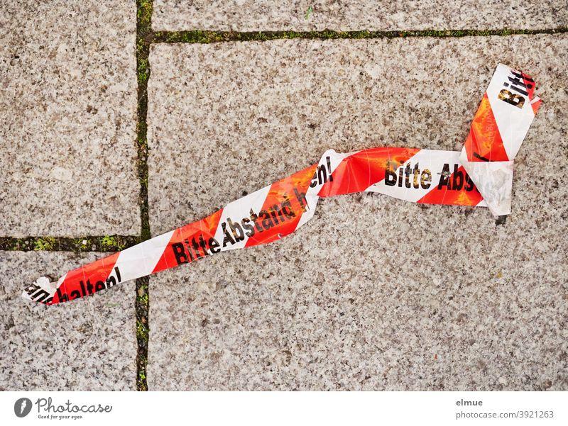 """rot-weißes Absperrband mit der Aufschrift """"Bitte Abstand halten"""" liegt zerknüllt auf dem grauen Betonpflaster / Corona Querdenker Coronakrise Prävention"""