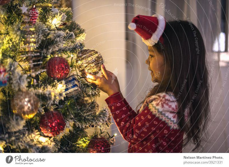 Kleines Mädchen in einem Weihnachtspulli und einer Weihnachtsmütze, die Weihnachtskugeln an den Baum hängen. Nizza offen schön Zauberei u. Magie Hintergrund