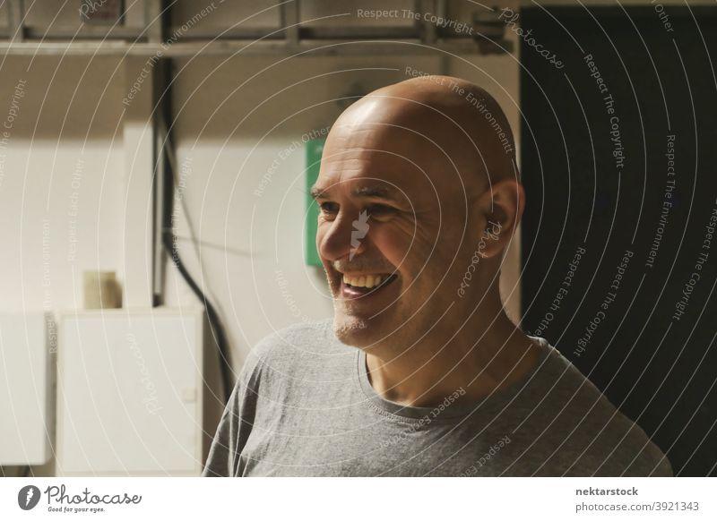 Kahlköpfiger Mann lächelnd in Garage Hintergrund kahl Kaukasier Arbeiter Werkstatt diy keine Haare 1 Mensch Handarbeit industriell Maschinenhalle Industrie