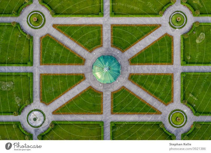 Symmetrische Luftaufnahme auf einen grünen Park mit einem Tempel in seiner Mitte, gerade von oben nach unten, beliebtes Architekturfoto. Antenne speziell