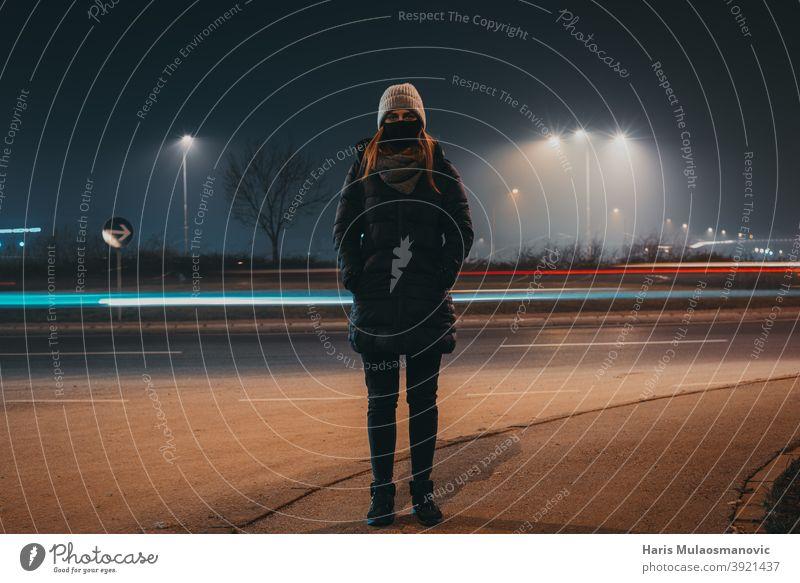 Frau mit Maske und Winterkleidung auf der Straße stehend, während Auto Lichter hinter vorbei, Zeit bewegen Konzept aktiv Aktivität Erwachsener Hintergrund schön
