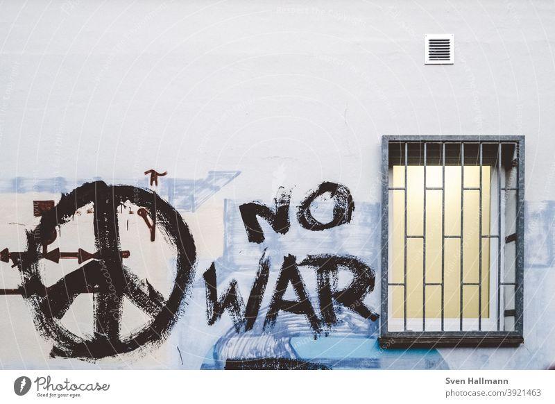 Graffiti an Wand mit Fenster Peace krieg frieden no war Krieg Frieden Gitter vergittert Gewalt grau Außenaufnahme Mauer Schriftzeichen Farbfoto Menschenleer