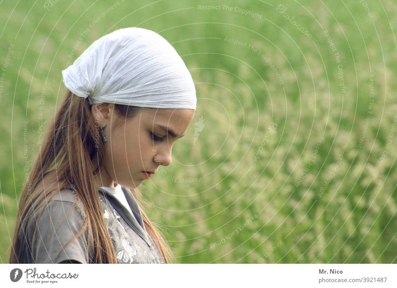 Junges Mädchen mit Kopfbedeckung blickt zu Boden Haare & Frisuren Oberkörper Mode Natur Kopftuch Gesicht Jugendliche Landschaft Wiese Lifestyle langhaarig Gras