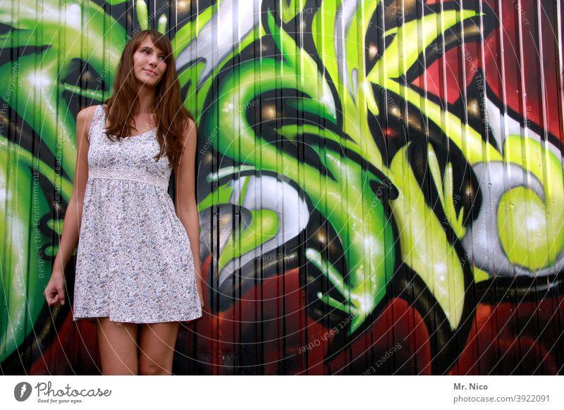 Junge Frau steht vor einer Grafitti Wand und schaut schüchtern nach links grafitti Sommerkleid Kunst Schriftzeichen Straßenkunst Fassade langhaarig Kultur grün