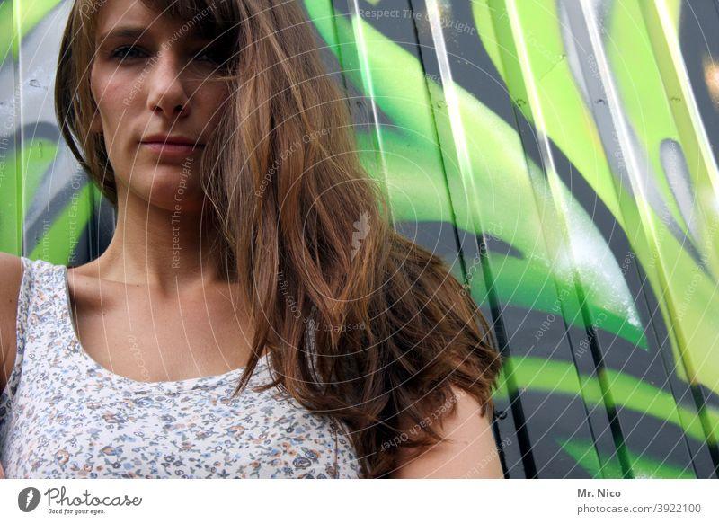Lange Haare fallen über die Schulter Frau Oberkörper selbstbewußt Coolness Ellenbogen stehen Kleid Körperhaltung feminin Mode schön langhaarig grafitti