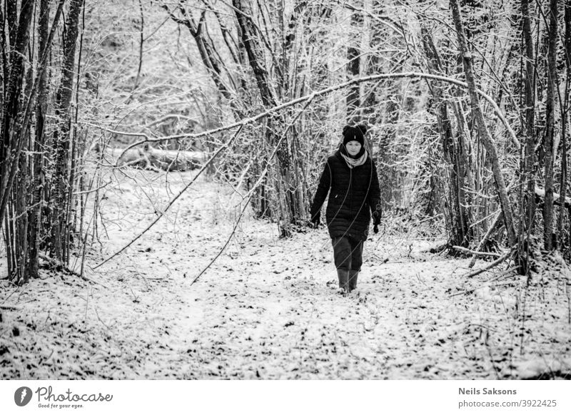 Frau zu Fuß im Wald im Winter Wald Schnee Winterwald kalt Baum Natur Landschaft Nachlauf Eis Haselnussstrauch warm angezogen gut gekleidet laufen Gummistiefel