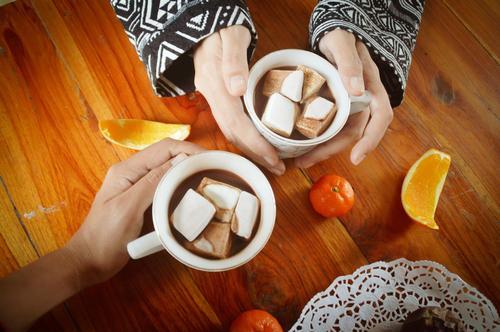 Teilen einer Tasse heißer Schokolade mit Marshmallow am Weihnachtsmorgen Silvester Zusammengehörigkeitsgefühl menschliche Verbindung heißes Schokoladengetränk