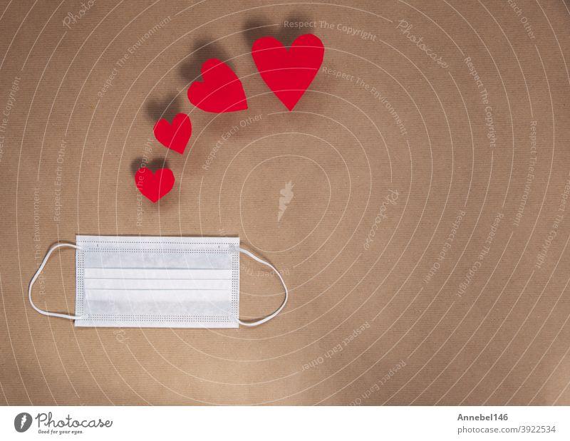Weiße medizinische Maske mit verschiedenen roten Herzen für Valentinstag und Coronavirus-Konzept, Kopierraum oder Platz für Text, Draufsicht modernes Design