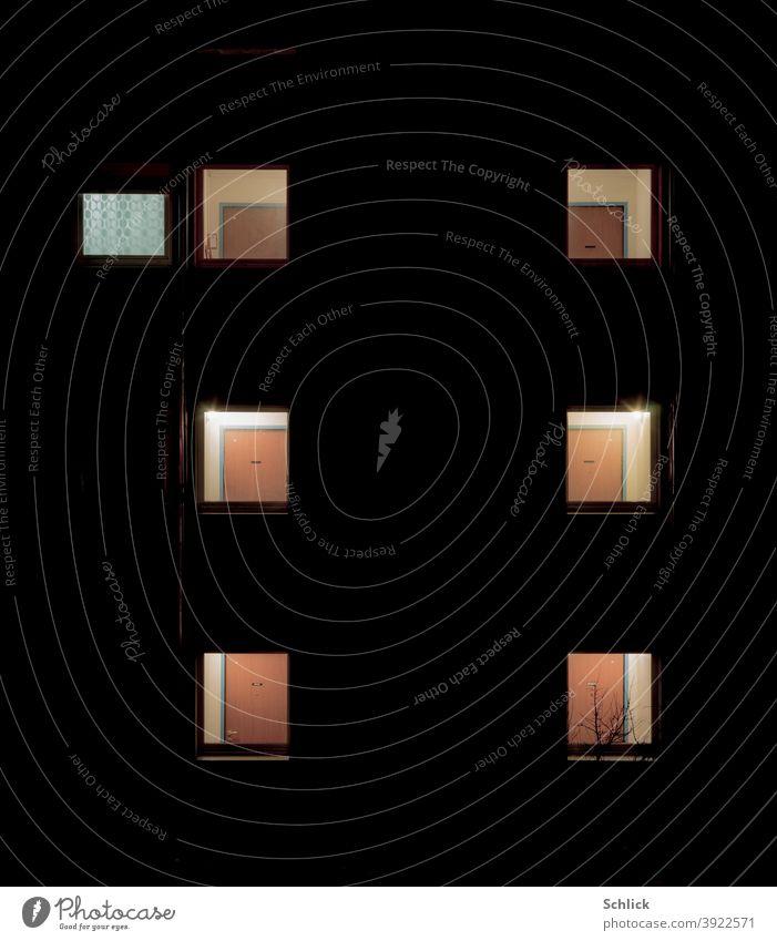Nachts erleuchtete Fenster mit Blick auf die Eingangstüren von Mietwohnungen und Flurfenster Fassade schwarz Holztüren Namensschilder Nummern Kunstlicht
