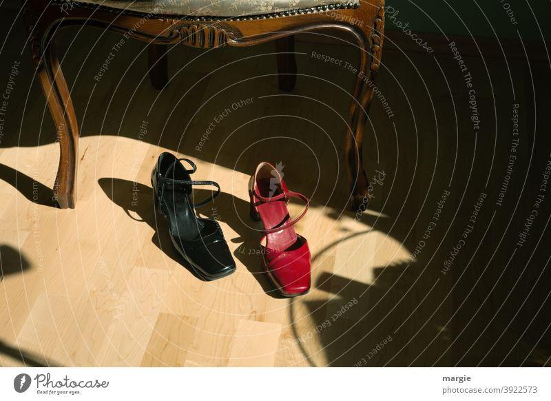 Ein paar Damen - Schuhe vor einem Stuhl, der eine Schuh ist rot, der andere schwarz fußboden Parkett Innenaufnahme Menschenleer Bodenbelag Damenschuhe feminin