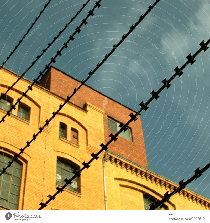 hinter Gittern Haus Stacheldraht Stacheldrahtzaun Backsteinfassade Backsteinhaus gelb diagonal Linie Zaun gefangen Schutz Sicherheit